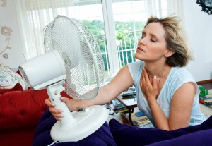 woman sweating and hot trying to cool down with fan
