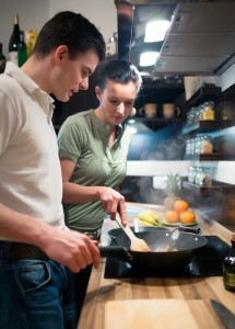 young couple in kitchen cooking healthy meal