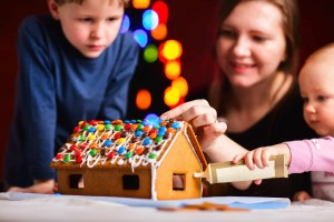 mother and children decorating holiday gingerbread house