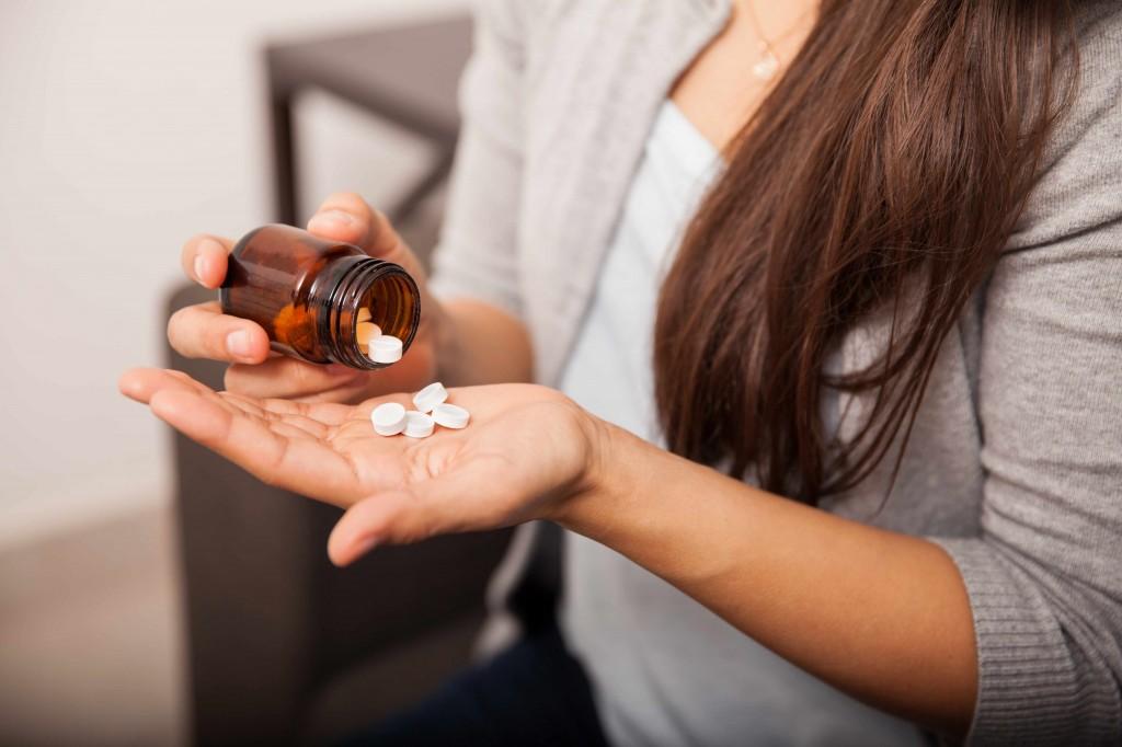 close up of woman putting aspirin pills into her hand