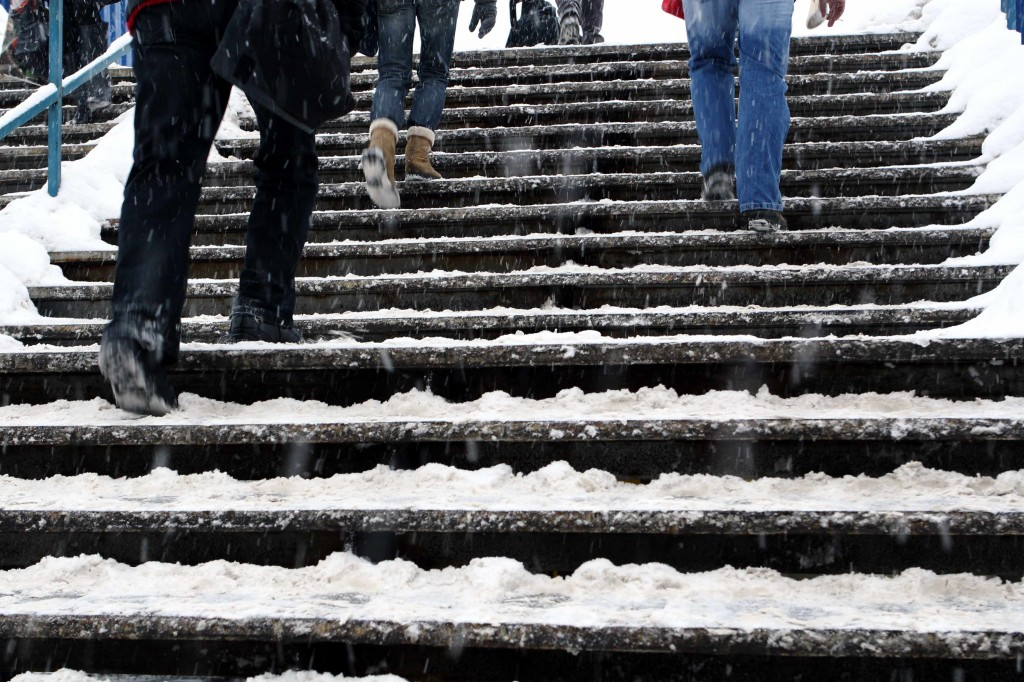 snow and ice covered steps with people walking