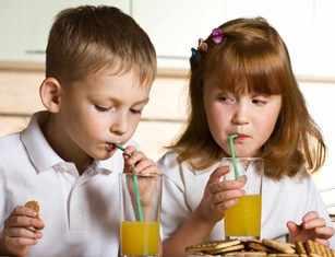 unos niños beben jugo de fruta
