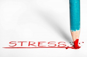 a red pastel pencil writing the word stress