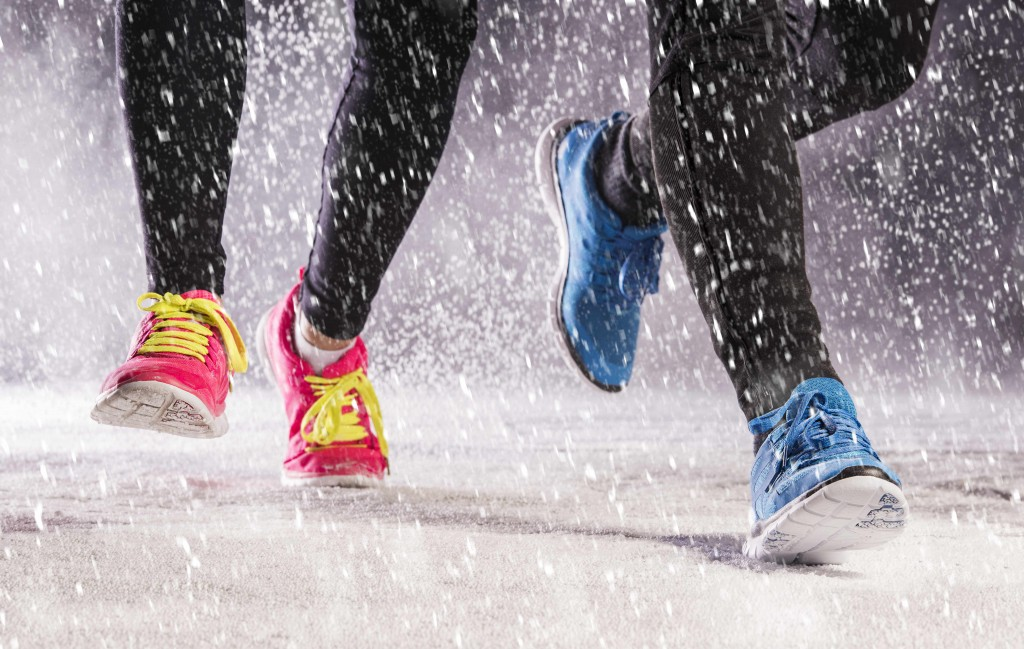 Athlete woman and man are running during winter training outside in cold snow weather.