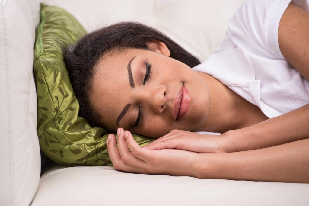 African-American woman sleeping or napping resting on pillow - diversity