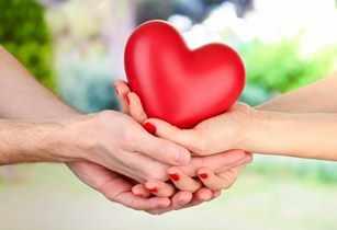 Corazón rojo en las manos de un hombre y una mujer