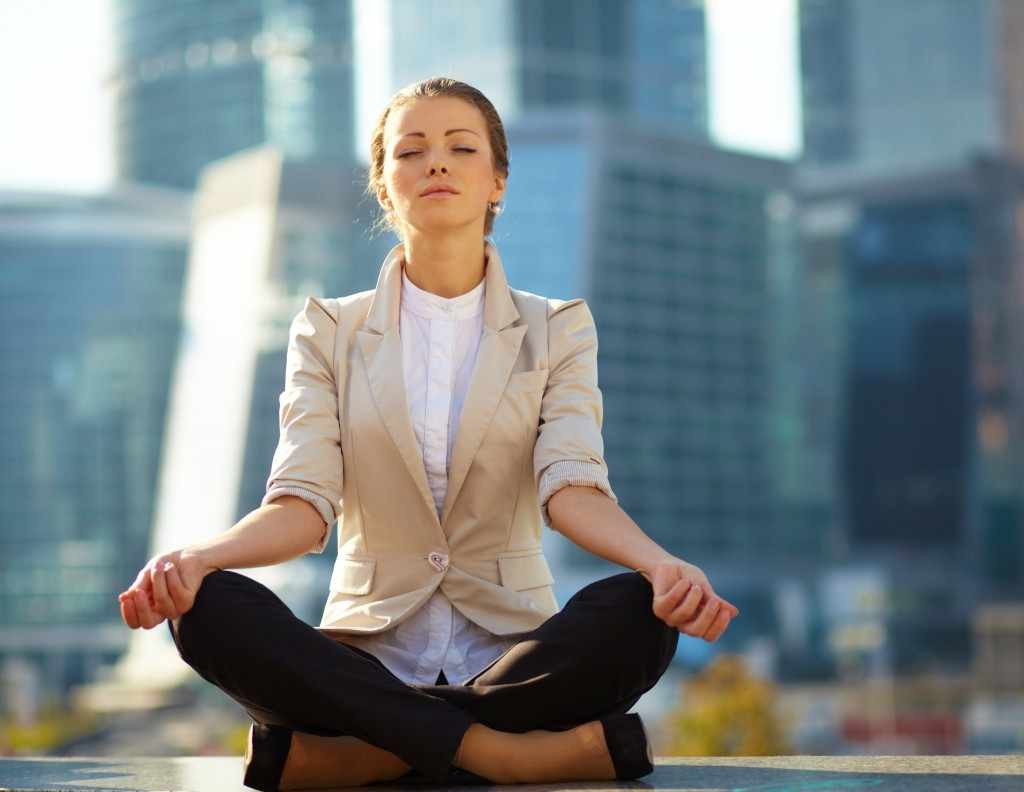 woman meditating, doing yoga, alternative medicine with city skyscrapers in the background