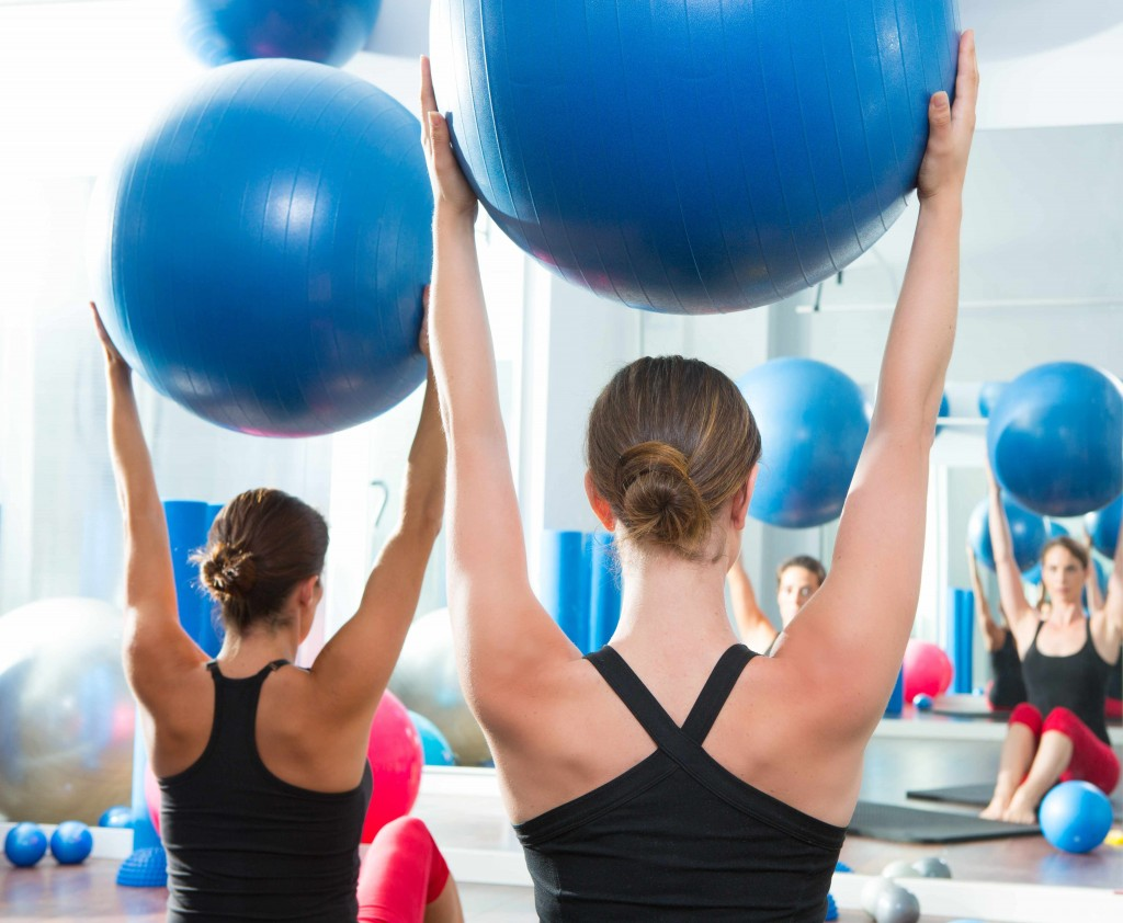 women using stability balls in a Pilates class