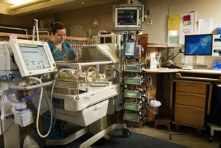 Una enfermera atiende a un neonato en la incubadora