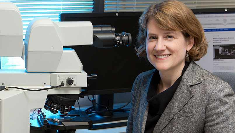 researcher Dr. Bobbi Pritt with lab microscope