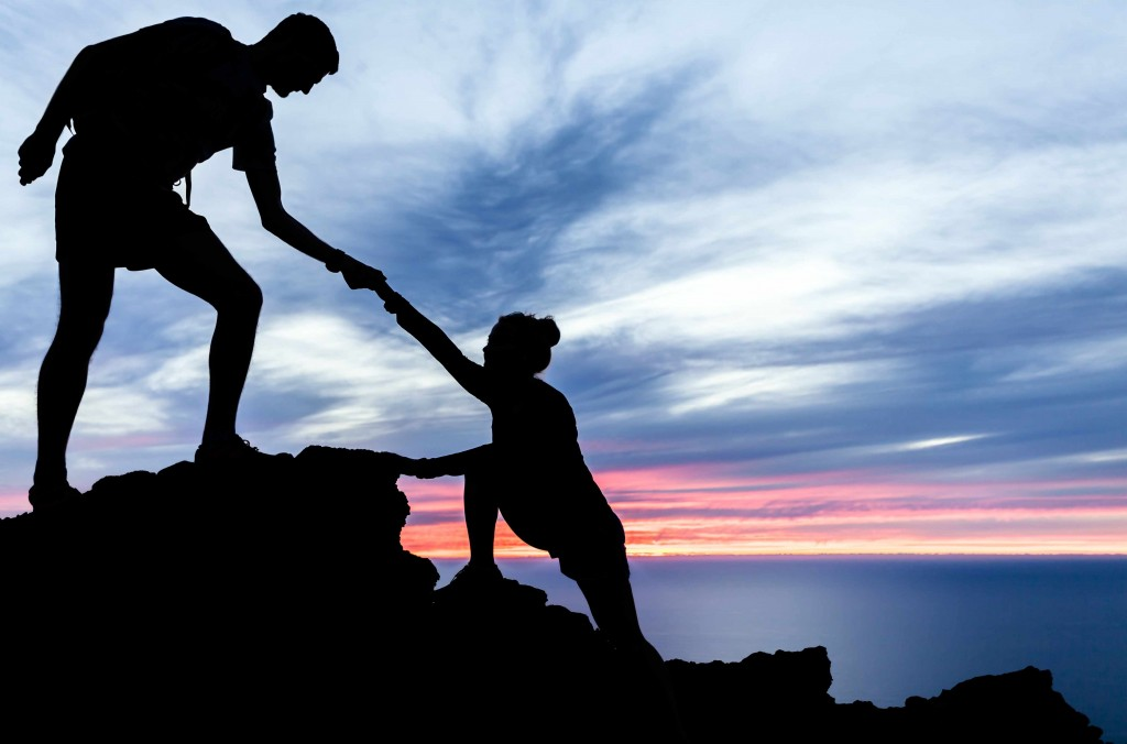 two people rock climbing, exercising, helping and trusting each other