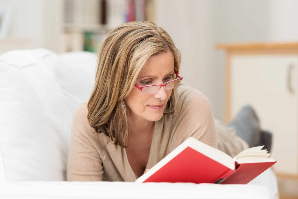 woman with glasses reading a book, vision