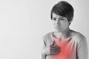 young woman with hand to chest appearing to have a heart attack, chest pain