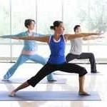 Dos mujeres y un hombre hacen yoga, en la pose del guerrero 2: los brazos extendidos, la pierna izquierda doblada en ángulo recto y la derecha estirada