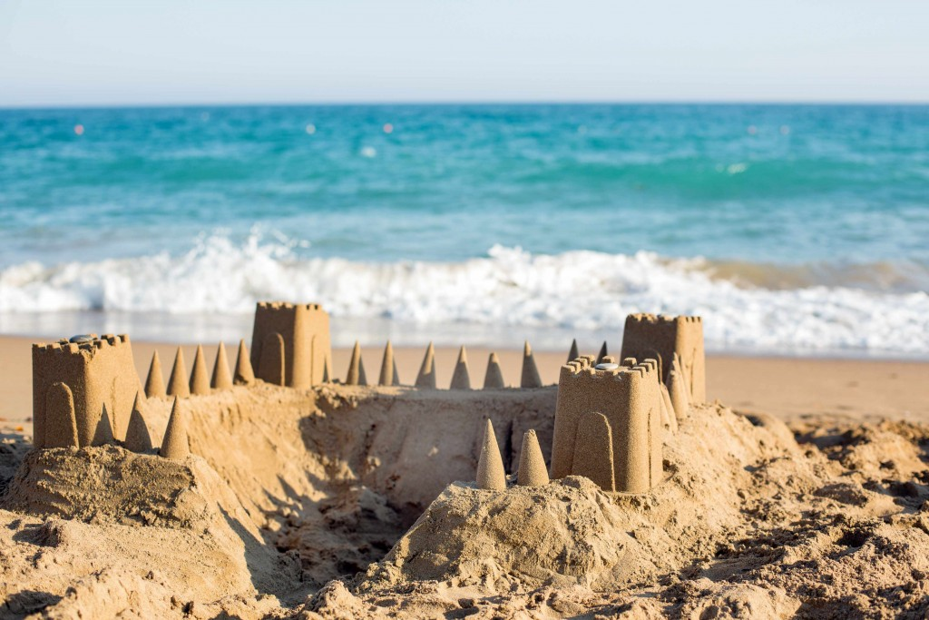sandcastle on the beach with the ocean waves in the background