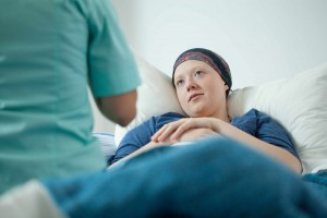 woman in bed resting, cancer patient with head scarf after chemotherapy