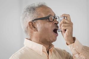 adult man using an inhaler for asthma