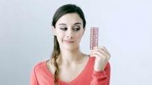 Una mujer contempla las pastillas anticonceptivas