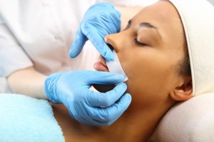 woman having lip hair removed with hot wax, cosmotology