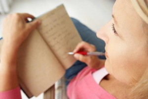 woman with pen writing in journal, feelings