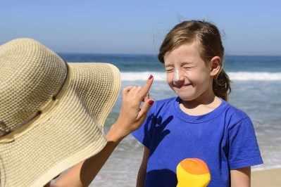Niña pequeña se asolea en la playa y una persona adulta le aplica protector solar en la nariz