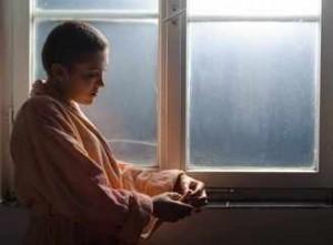 Paciente joven con cáncer piensa junto a la ventana