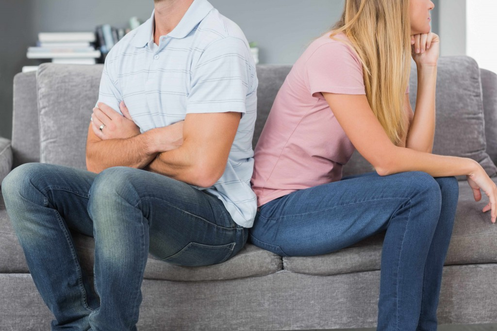 man and woman sitting back to back after argument, hurting each other