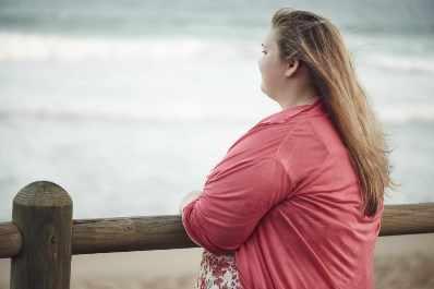 Mujer joven con exceso de peso mira pensativa el mar