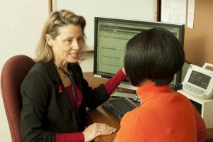 physician speaking with patient and looking at computer screen for medical test results