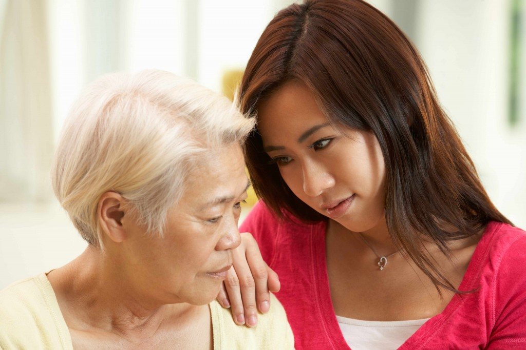 young Asian woman comforting older woman who is sad