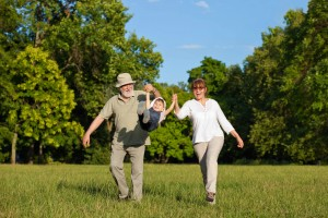 middle aged couple walking and exercising, having fun with child