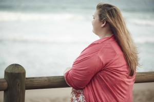 young overweight woman looking out at the ocean and thinking