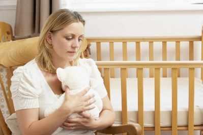 Mujer triste sentada frente a una cuna vacía en la sala de recién nacidos