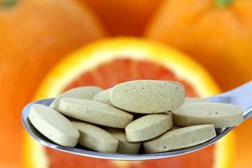 Suplementos de vitamina C con naranjas y frutas cítrica en el fondo