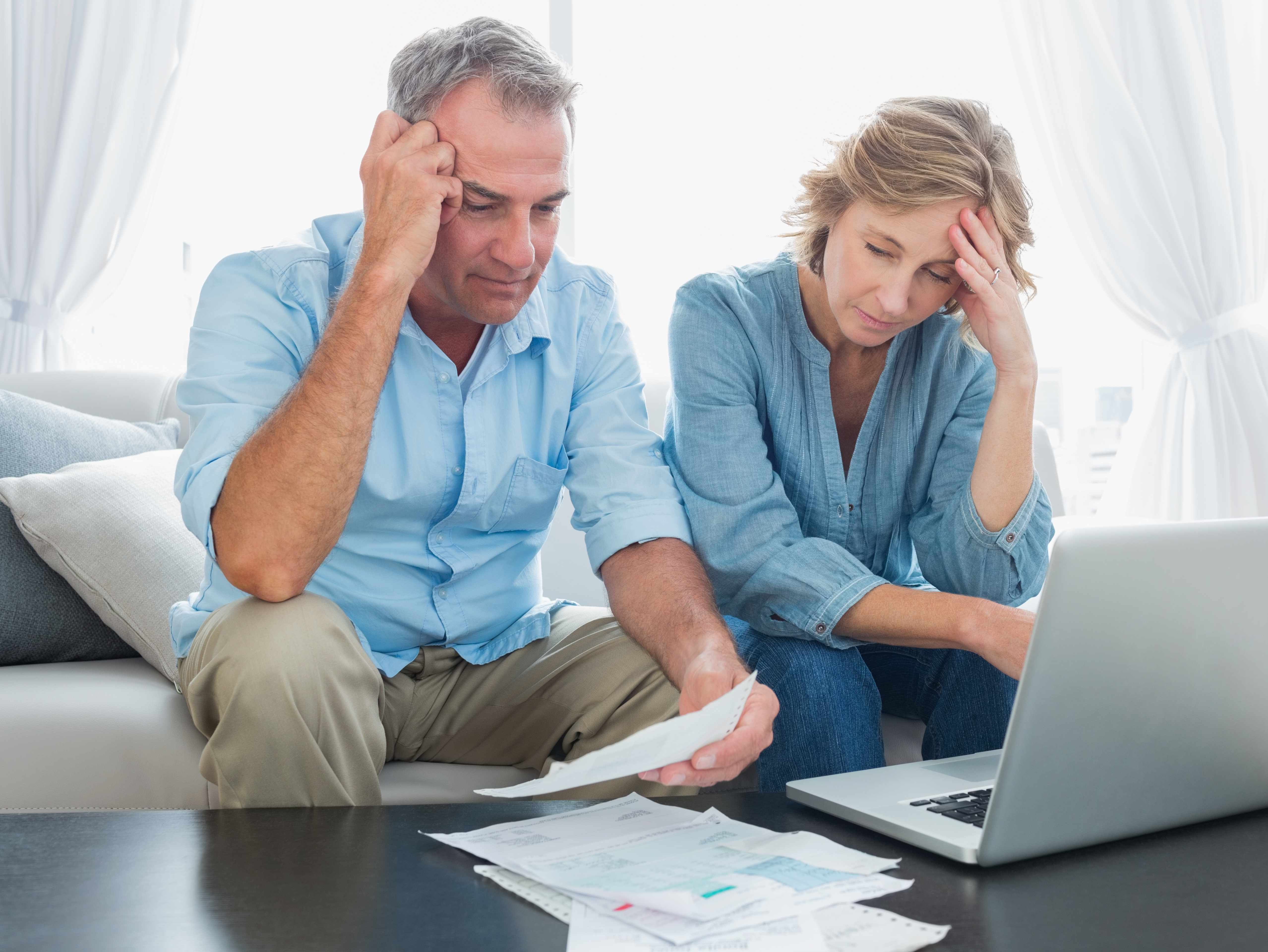 man and woman, couple, sitting at computer worried and concerned about finances