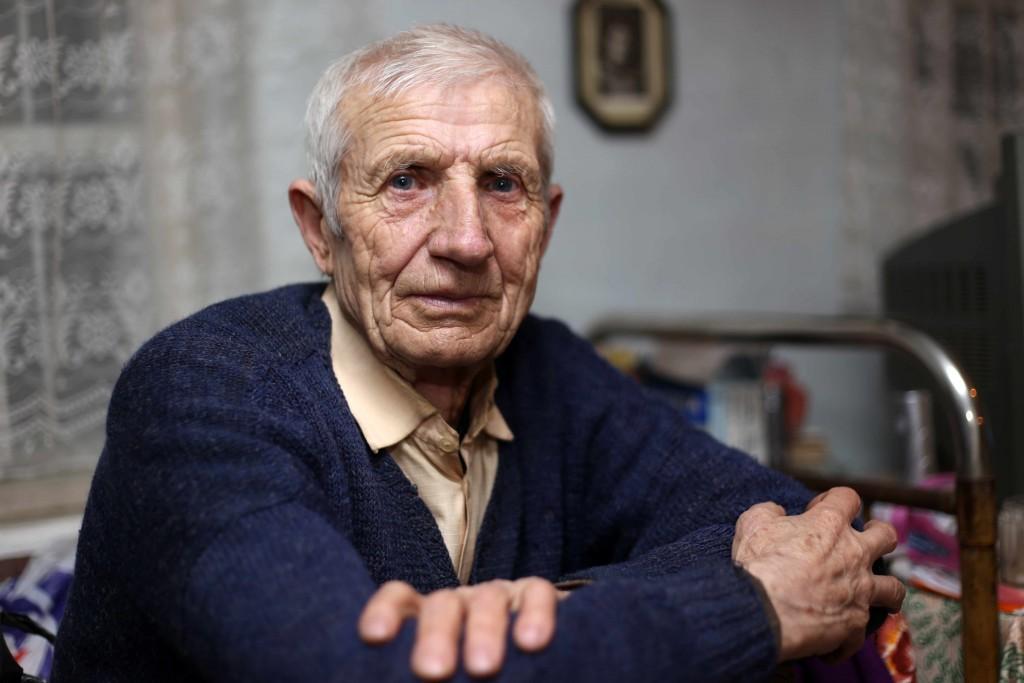 senior citizen, older man sitting at table