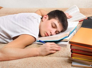 young teenage boy asleep on his schoolbooks