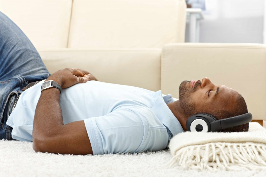 man relaxing with music on headphones at home, lying on floor.