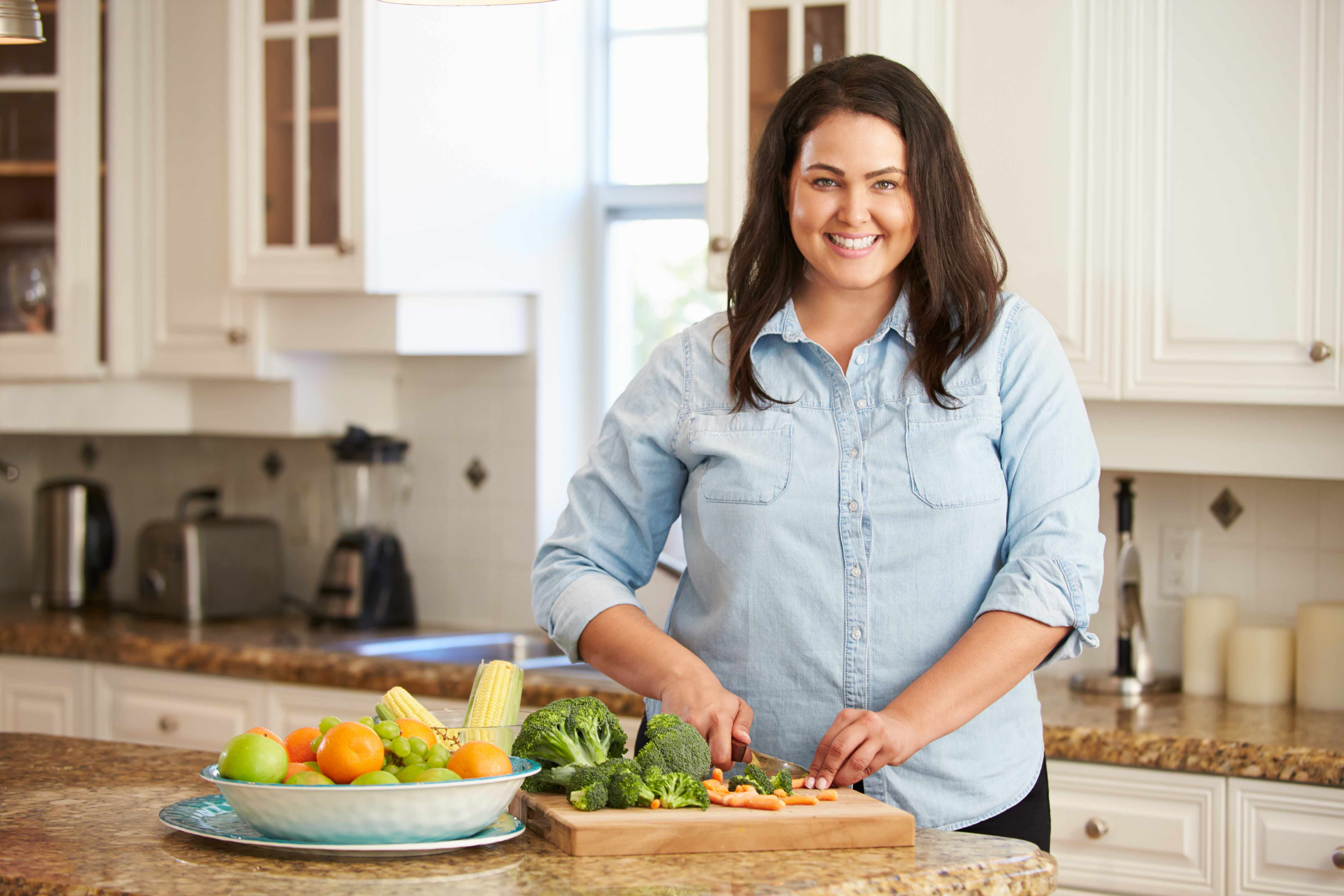 woman in kitchen cutting up healthy vegetables
