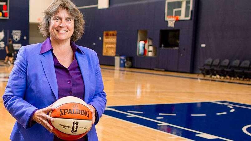 Minnesota Lynx basketball coach Nancy Cummings standing on a basketball court, holding a basketball