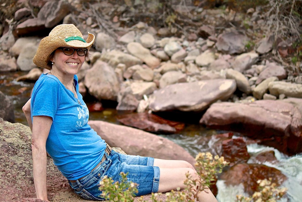 Woodside Christina smiling while sitting on the bank of a river