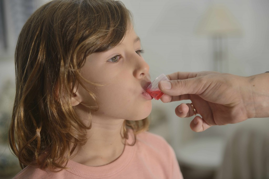 little girl taking medicine, antibiotic or cough syrup