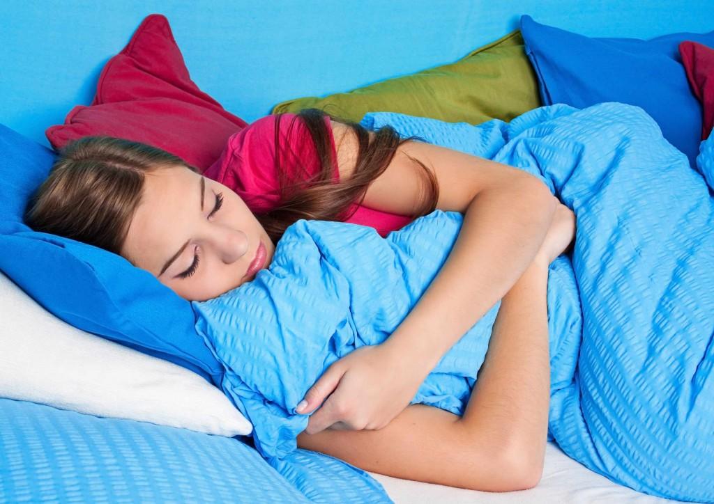 teenage girl sleeping, wrapped in blankets
