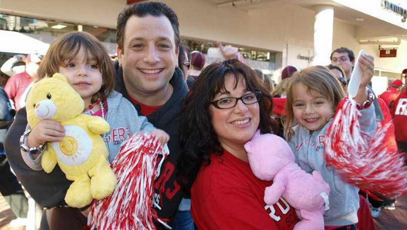 Scott Borden Family photo, wife and little girls holding stuffed animals and pom-poms
