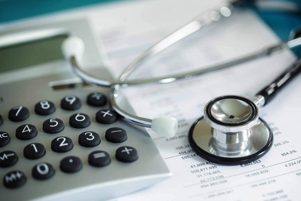 medical records, paperwork with calculator and stethoscope