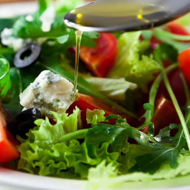 editerranean salad with black olives, cheese, bright red tomatoes with olive oil dripping from a spoon