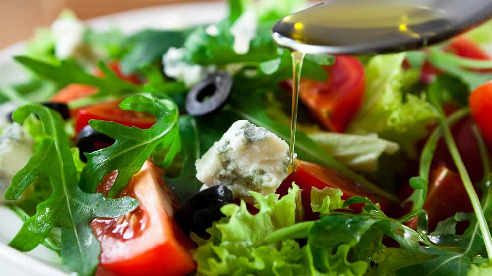 Mediterranean salad with black olives, cheese, bright red tomatoes with olive oil dripping from a spoon