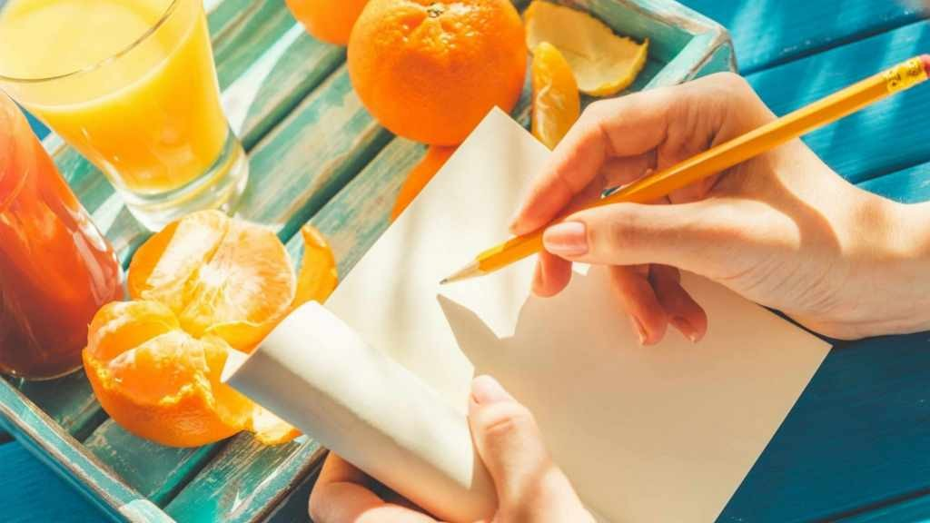 woman writing in food diary