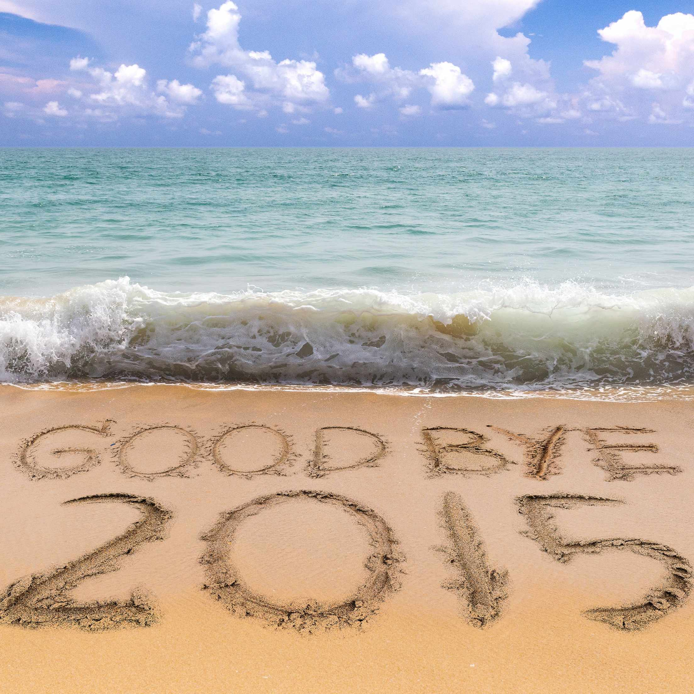 goodbye 2015 written in beach sand with waves in background