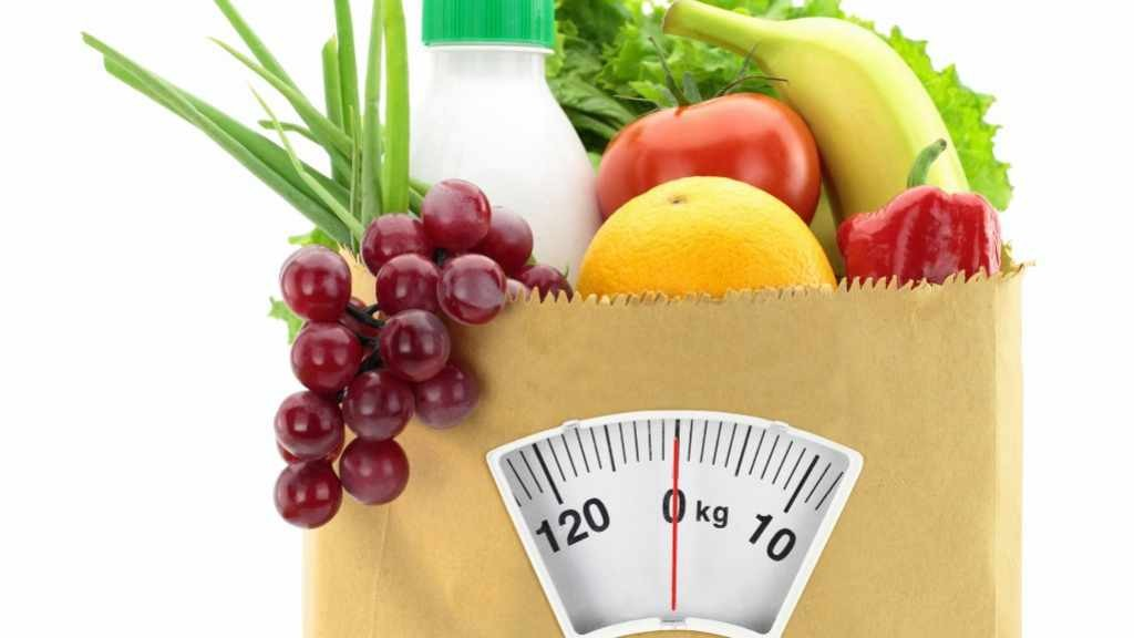 healthy food in grocery bag with scale dial at bottom of bag